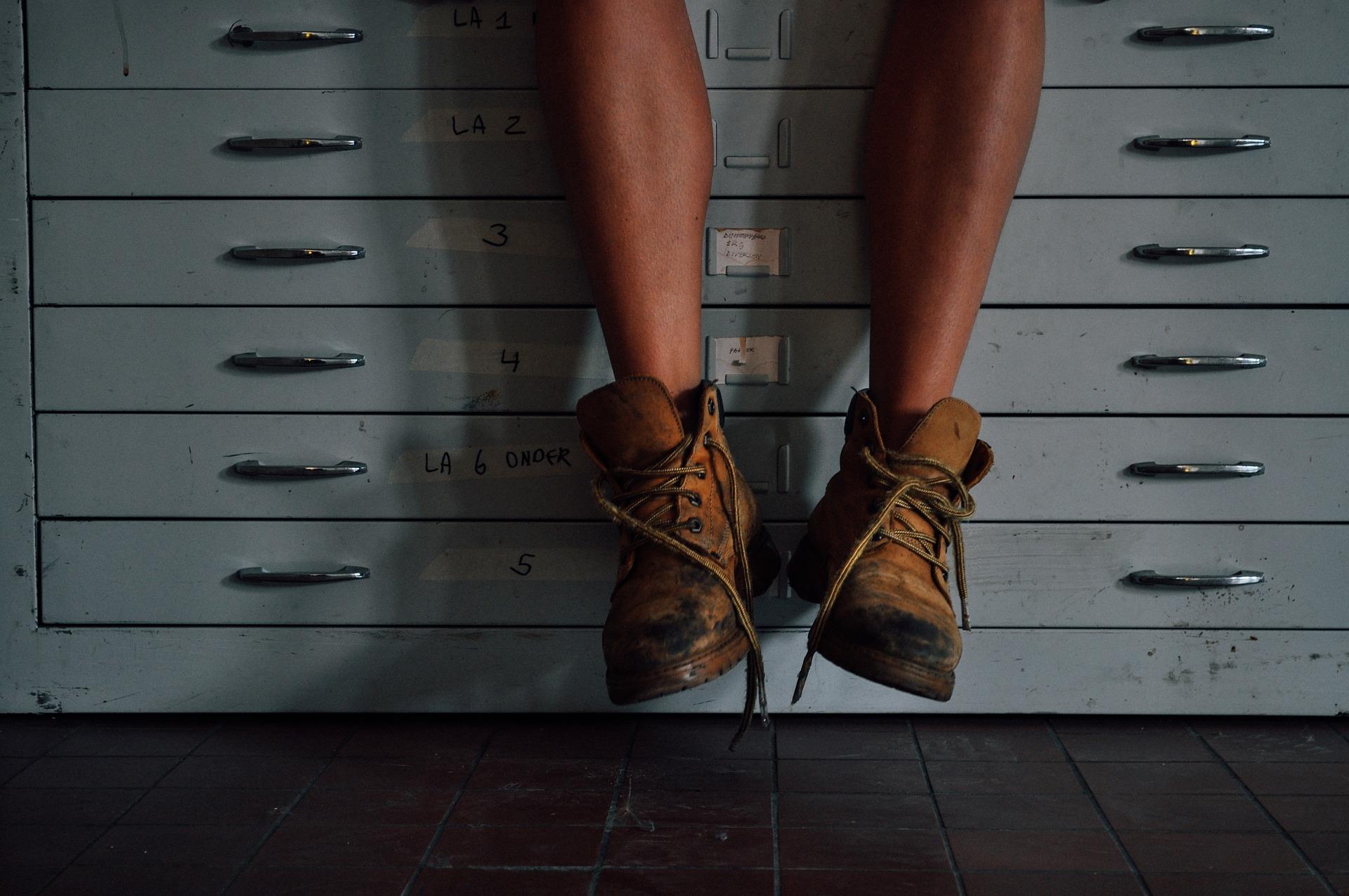 Symbolbild EPU baumelnde Beine auf Büromöbel